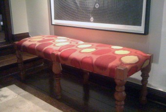 An Upholstered Bench with Eccentric Turned Legs